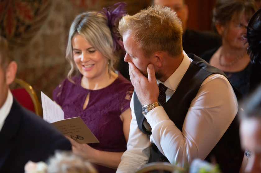 smiling lady in purple dress reading order of service booklet with her husband looking on with interest