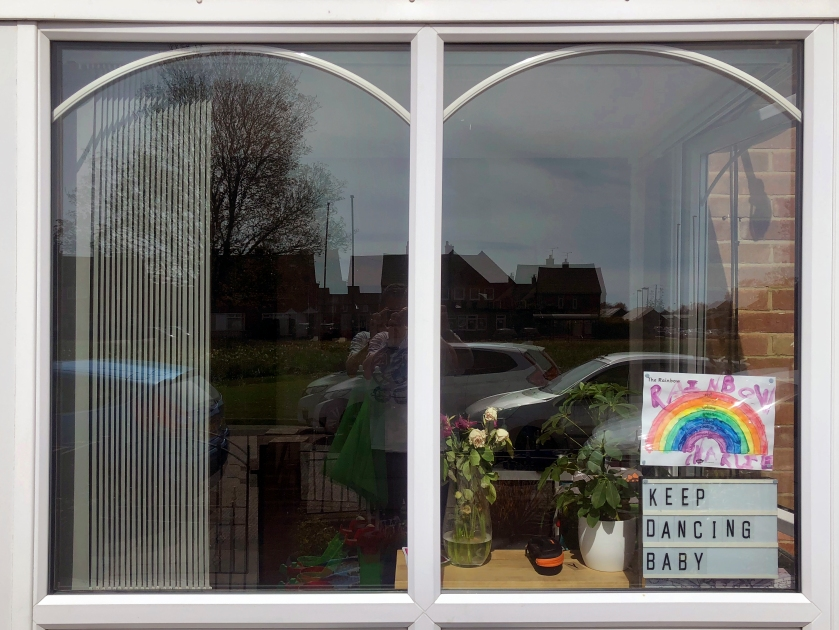 Window displaying lightbox and rainbow with quote Keep Dancing Baby