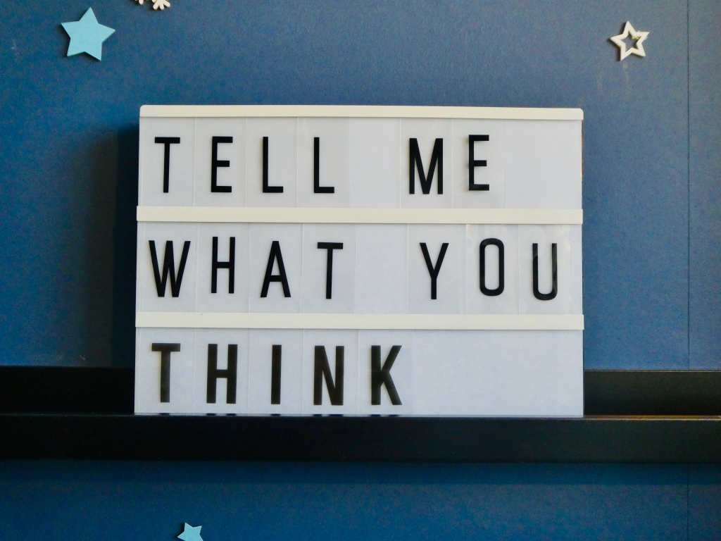 Lightbox quote displaying 'Tell me what you think' with navy blue background and stars