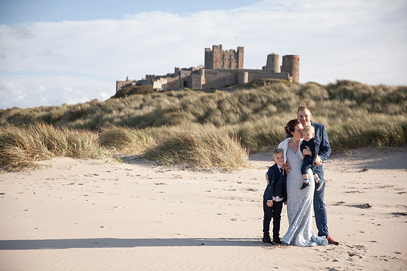 bride, groom and children standing on Bamburgh Beach with castle in background