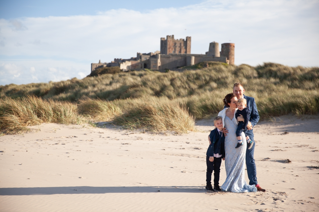 Bride in blue wedding dress groom children stood on Bamburgh beach, Northumberland with sand dunes castle in the background