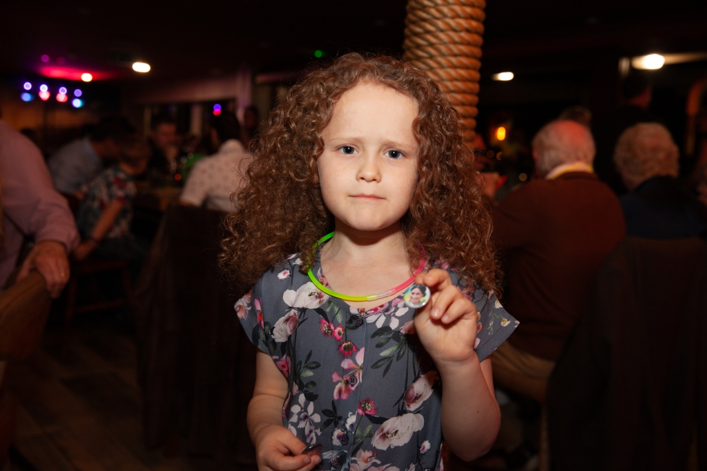 Girl with glow stick around neck holding pin badge of meghan markle