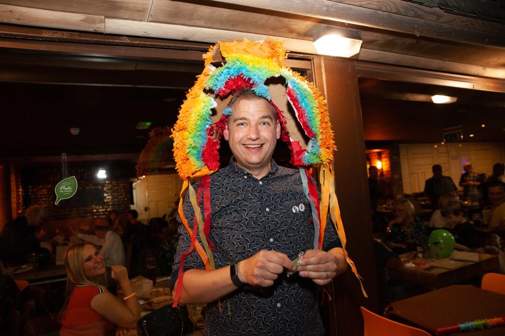Rainbow piñata on head of groom
