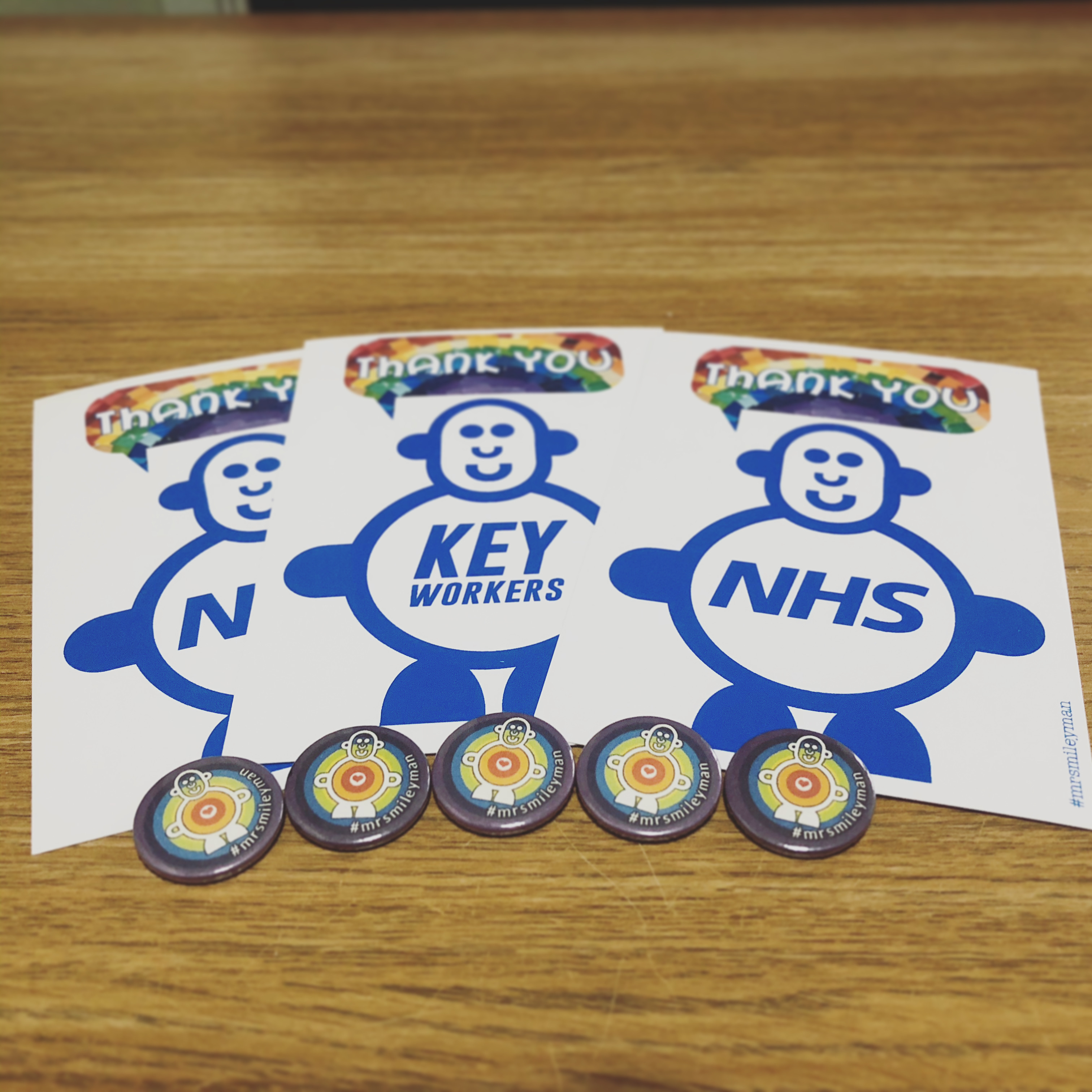 Postcards and pin badges displaying cute smileyman character and thank you message
