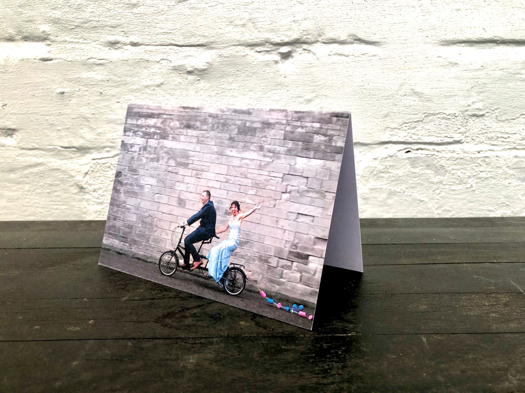 Bride in blue dress, groom riding tandem bike on thank you card